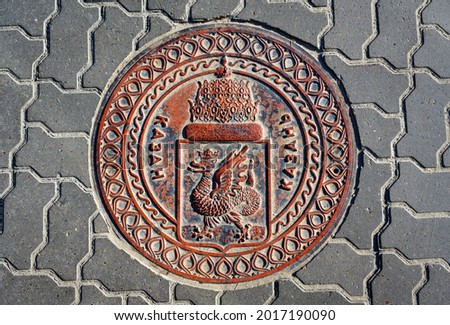 Manhole cover in Kazan, Tatarstan, Russia. Sewer lid with coat of arms of Kazan on road. Top view of metal manhole cap on city street. Traditional dragon emblem and word Kazan on old drain plate. Royalty-Free Stock Photo #2017190090