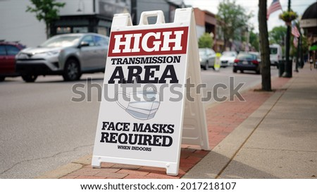 """A sign on the sidewalk on a small town's main street warns people that this is a """"high transmission"""" area for COVID-19. The CDC again required face masks when the delta variant surged in 2021."""