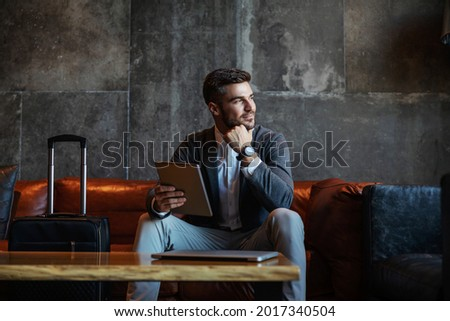 Good looking businessman sitting on a hotel couch and holding the tablet. Next to him is a suitcase. He is wearing an elegant blazer, white shirt, grey pants, and an expensive watch.Business trip Royalty-Free Stock Photo #2017340504