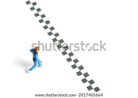 Miniature people toy figure photography. A young man running towards the finish line, isolated on white background. Image photo