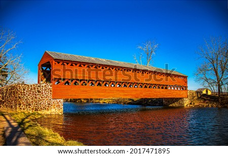 Red wooden covered bridge over the river. Covered bridge over river. River covered bridge. Red covered bridge over river Royalty-Free Stock Photo #2017471895