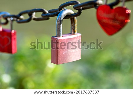 A pink padlock hanging on a chain engraved with the words love forever.