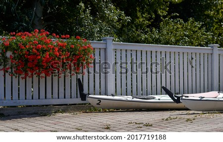 white kayaks on the background of a white wooden fence, pots with flowers on the fence . High quality photo Royalty-Free Stock Photo #2017719188