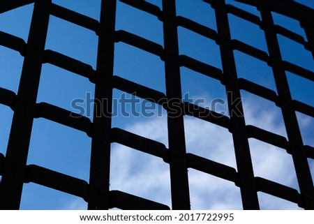 Selective focus, texture of a metal old lattice fence against the blue sky, fence lattice, lattice background, cell. High quality photo Royalty-Free Stock Photo #2017722995