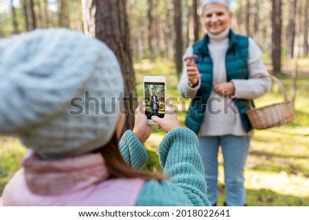 picking season, leisure and people concept - granddaughter with smartphone photographing happy smiling grandmother with mushrooms in basket in forest