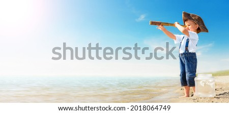 Kid play on the beach on a hot sunny day. Little girl dressed as a pirate stands barefoot on the sandy seashore with a telescope. Child with a toy fish dreams of travel and adventure. Royalty-Free Stock Photo #2018064749