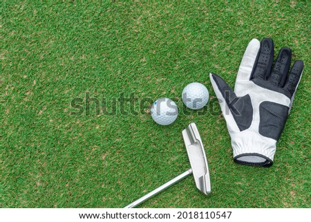 golf glove , white golf ball and tee put on green grass of golf course ,This golf objects for play Royalty-Free Stock Photo #2018110547