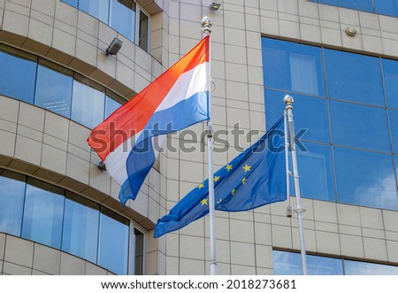 Flags of the Netherlands and European Union on flagpole waving during windy day. Netherlands and EU flags on the flagpole.  Royalty-Free Stock Photo #2018273681