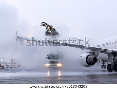 De-icing procedure for big airliner at the international airport. Winter, overcast, cold weather. Large clouds of steam. Jets of sprayer. Special airfield equipment. Ice prevention. Aviation safety.