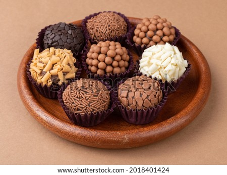 Typical brazilian brigadeiros, various flavors on a wooden plate. Royalty-Free Stock Photo #2018401424