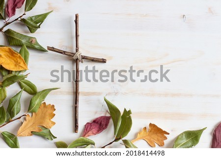 Wood cross with autumn leaf border on white wood background  Royalty-Free Stock Photo #2018414498