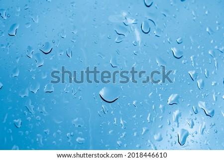 Raindrops on the window. Blue tone Royalty-Free Stock Photo #2018446610
