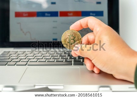 Man holding a physical currency: Bitcoin in front of laptop with a background of stock market charts. Concept of new investments in virtual currencies . High quality photo