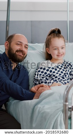 Family watching cartoon movie on television in hospital ward while waiting for medical sickness expertise during healthcare examination. Sick child patient resting in bed after medicine surgery