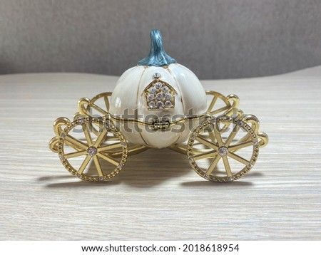 Statuette in the form of a pumpkin carriage on golden wheels close-up Royalty-Free Stock Photo #2018618954