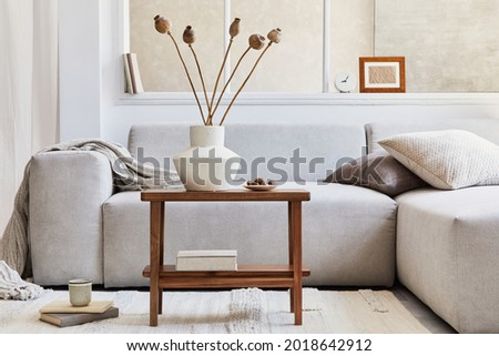Creative composition of stylish living room interior with grey corner sofa, window, wooden coffee table, vase with dried flowers and personal accessories. Beige neutral colors. Template. Royalty-Free Stock Photo #2018642912