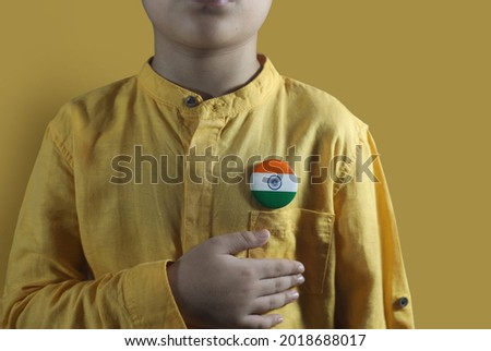Young boy hand on chest with Indian flag emblem Royalty-Free Stock Photo #2018688017