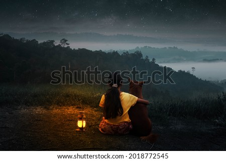A little girl snuggled up to her dog and watched the stars at night alone by the light of the lantern.