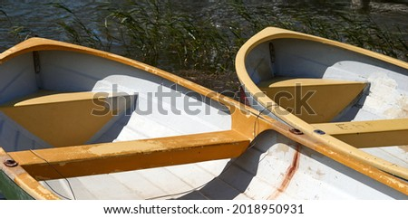 2 row boats side by side docked at a lake in summer. High quality photo Royalty-Free Stock Photo #2018950931