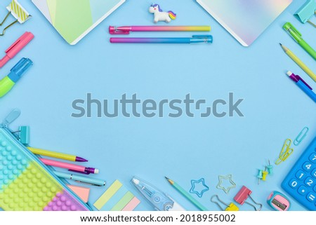 Back to School frame with copy space. Collection of colorful school supplies in a bright flat style. Educational concept. Unicorn, calculator, pencil case, pencils, sharpeners and curly paper clips. Royalty-Free Stock Photo #2018955002