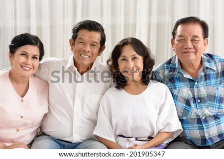 Portrait of four Vietnamese retired people sitting on the sofa and looking at the camera #201905347