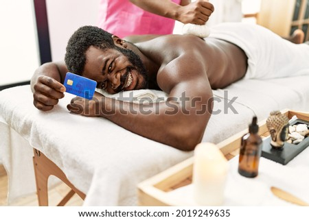 Young african american man reciving herbal pouches thai massage and holding credit card at beauty center.