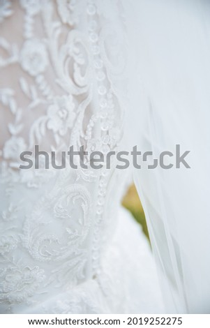 Gentle picture of a bride standing from behind. Close up of bride dress. White lace dress.