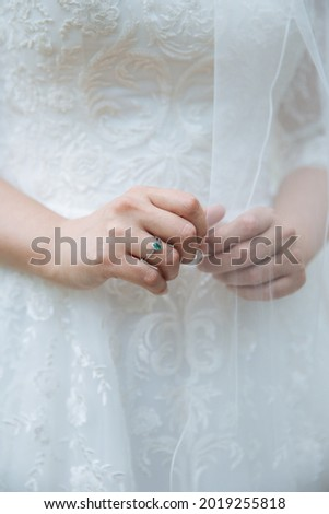 Gentle picture of a bride standing with beautiful green weeding ring. Close up of bride dress. White lace dress. Unique wedding ring.