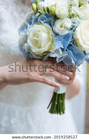 Gentle picture of a bride standing with beautiful green weeding ring holding blue bouquet. Close up of bride dress. White lace dress. Unique wedding ring.