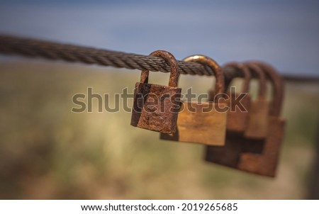 A number of padlocks hanging on steel wire. Shallow depth of field. They are considered as love symbols.