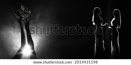 Silhouette abstract of two hands try to reach Diamond Crown as Miss Beauty Queen Pageant Contest as final competition, finale winner moment hold hand together. Backlit smoke copy space Royalty-Free Stock Photo #2019431198