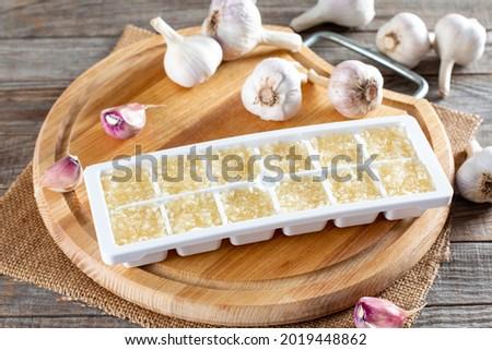 Frozen garlic. Frozen garlic puree on wooden table. Frozen food Concept Royalty-Free Stock Photo #2019448862