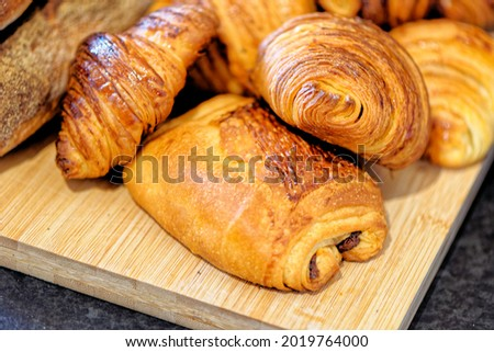 Fresh croissants and pain au chocolate, puff pastry and buttered french croissant on a plate. Food and breakfast concept. Detail of desserts and fresh pastries Royalty-Free Stock Photo #2019764000