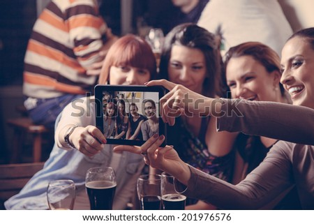 Young Cheerful Female Friends Taking Selfie In Pub Using Digital Tablet