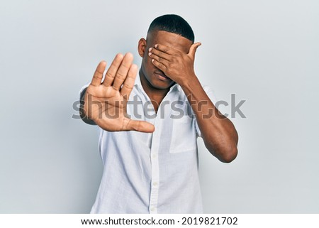 Young black man wearing casual white shirt covering eyes with hands and doing stop gesture with sad and fear expression. embarrassed and negative concept.