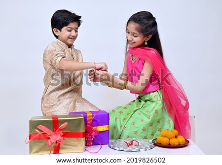 Hindu Brother and sister  in ethnic wear holding Indian sweets and gift box on the occasion of Raksha Bandhan festival Royalty-Free Stock Photo #2019826502