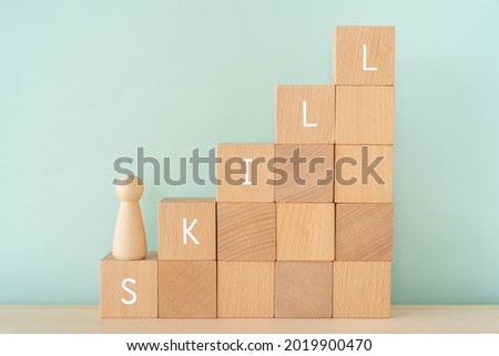 """SKILL; Wooden blocks with """"SKILL"""" text of concept and a human toy. Royalty-Free Stock Photo #2019900470"""