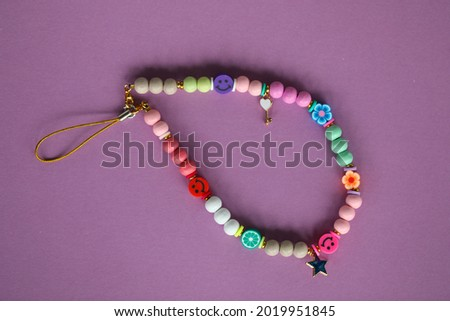 A cute phone charm made with wooden beads and charms.  Royalty-Free Stock Photo #2019951845