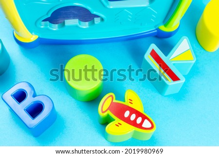 Children's background. Educational toy sorter in the form of a cube with bright figures (letter, boat, plane) on a blue background. Development of fine motor skills and thinking of the baby