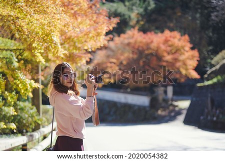An asian woman traveler wearing glasses using her camera taking photo, turn right to looking camera with little smile with red, orange and yellow colors of maple leaf bokeh.