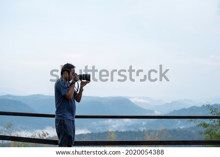 Male photographer using his camera taking a view, profressional, traveling concept.