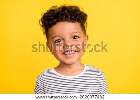 Photo portrait cheerful small boy smiling in striped shirt isolated bright yellow color background Royalty-Free Stock Photo #2020077482