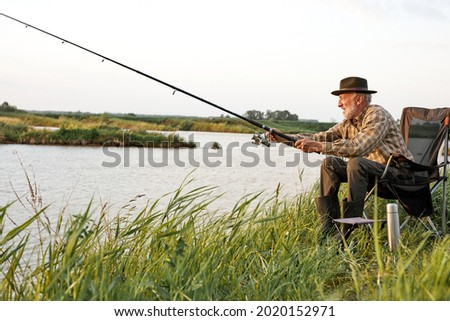Side view on elderly gray-haired man fishing on lake in nature, patience and recreation concept.Portrait of senior caucasian fisherman with rod sitting on chair in nature, countryside Royalty-Free Stock Photo #2020152971