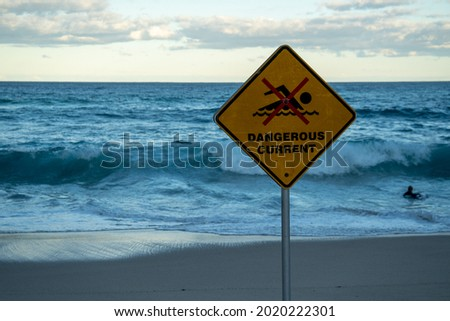 danger sign on the beach saying dangerous current no swimming