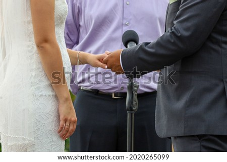 Picture of bride and groom getting married and holding hands.