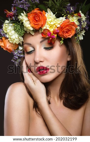 Beautiful girl with perfect skin and bright floral wreath on her head. Picture taken in the studio on a black background #202032199