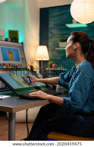 Photography designer working on image with stylus and touch interface to edit at studio agency. Woman with modern creativity equipment using monitor computer app professional technology