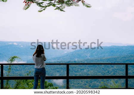 A photographer turning back to camera and using her camera taking mountain view at view point while traveling.