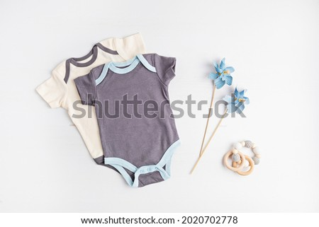 Mockup of gender neutral baby garment. Organic cotton clothes, newborn fashion, branding, small business idea. Flat lay, top view Royalty-Free Stock Photo #2020702778