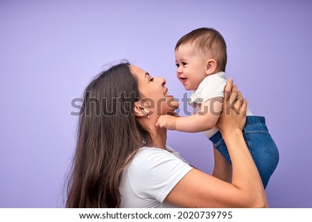 Beautiful young caucasian mother tossing up child baby. Baby laughing. Purple background. In studio. Copy space, side view. Portrait of caucasian family. Happy childhood concept Royalty-Free Stock Photo #2020739795